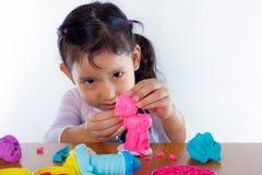La petite fille apprend à employer la pâte colorée de jeu Image libre de droits