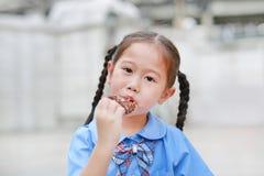La petite fille asiatique adorable d'enfant dans l'uniforme scolaire ont plaisir à manger la glace à la vanille de chocolat photos stock