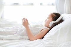 La petite fille asiatique de portrait utilisant des écouteurs écoutent musique par le smartphone tout en se trouvant sur le lit à images stock
