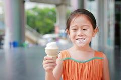 La petite fille asiatique de sourire d'enfant ont plaisir à manger le cornet de crème glacée avec des taches autour de sa bouche image libre de droits