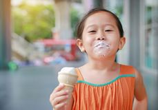 La petite fille asiatique de sourire d'enfant ont plaisir à manger le cornet de crème glacée avec des taches autour de sa bouche photo stock