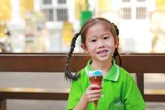 La petite fille asiatique de sourire d'enfant ont plaisir à manger le cornet de crème glacée avec des taches autour de sa bouche photographie stock libre de droits