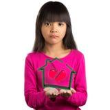 La petite fille asiatique de tristesse tenant la maison virtuelle avec cassé entendent Photographie stock libre de droits