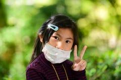 La petite fille asiatique est fatigué avec le bokeh vert images libres de droits