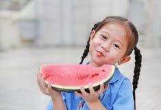 La petite fille asiatique heureuse d'enfant dans l'uniforme scolaire ont plaisir à manger la pastèque dehors photo stock