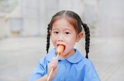 La petite fille asiatique heureuse d'enfant dans l'uniforme scolaire ont plaisir à manger la saucisse dehors photographie stock libre de droits