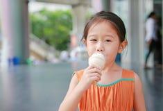 La petite fille asiatique heureuse d'enfant ont plaisir à manger le cornet de crème glacée avec souillé autour de sa bouche photos libres de droits
