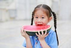 La petite fille asiatique mignonne d'enfant dans l'uniforme scolaire ont plaisir à manger la pastèque coupée en tranches fraîche photographie stock