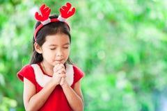 La petite fille asiatique mignonne dans la robe de Noël a fermé ses yeux Photo stock