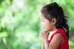 La petite fille asiatique mignonne dans la robe de Noël a fermé ses yeux Photos stock