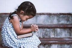 La petite fille asiatique mignonne a fermé ses yeux et a plié sa main Images libres de droits