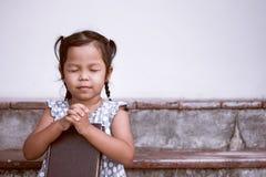 La petite fille asiatique mignonne a fermé ses yeux et a plié sa main Image libre de droits