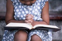 La petite fille asiatique mignonne a fermé ses yeux et a plié sa main Photo libre de droits