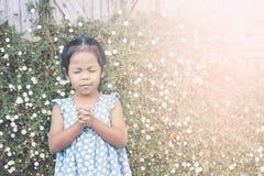 La petite fille asiatique mignonne a fermé ses yeux et a plié sa main Photographie stock