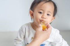 La petite fille asiatique prend le sirop de médecine avec sa mère images stock