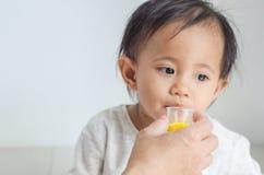 La petite fille asiatique prend le sirop de médecine avec sa mère Photo stock