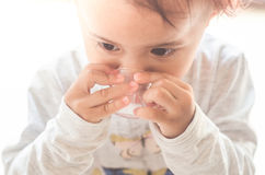 La petite fille asiatique prend le sirop de médecine seule photo stock
