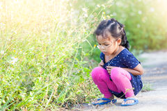 La petite fille asiatique s'asseyant regardant l'herbe avec soit expression triste images libres de droits