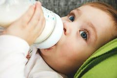 La petite fille aux yeux bleus boit du lait d'une bouteille se trouvant sur le lit photographie stock