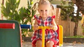 la petite fille avec des hairtails bascule sur l'oscillation sur le terrain de jeu en parc banque de vidéos