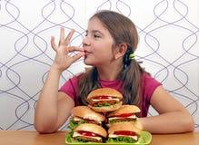 La petite fille avec des hamburgers et la main correcte signent Photo libre de droits