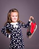 La petite fille avec des joueurs de hockey patinent dans la main Image libre de droits