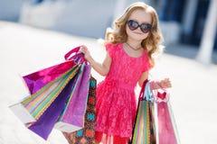 La petite fille avec des paniers va au magasin Images stock