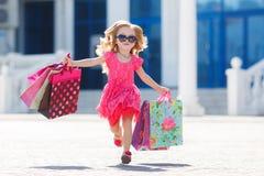 La petite fille avec des paniers va au magasin Photographie stock libre de droits