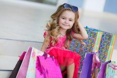 La petite fille avec des paniers va au magasin Photo stock