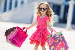 La petite fille avec des paniers va au magasin Image stock