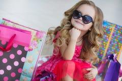 La petite fille avec des paniers va au magasin Photo libre de droits
