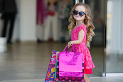 La petite fille avec des paniers va au magasin Photos libres de droits