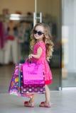 La petite fille avec des paniers va au magasin Images libres de droits