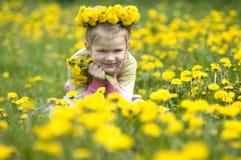 La petite fille avec des pissenlits Photographie stock libre de droits