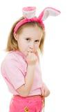 La petite fille avec des regards roses de lapin d'oreilles a blessé Photographie stock libre de droits