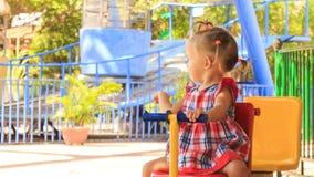 la petite fille avec des roches de hairtails sur l'oscillation ondule la main en parc banque de vidéos