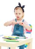 La petite fille avec du charme dessine avec des marqueurs tandis que Images libres de droits