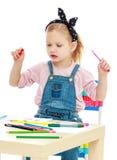 La petite fille avec du charme dessine avec des marqueurs tandis que Image stock