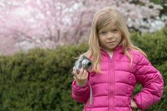 La petite fille avec l'appareil-photo de photo en parc de fleurs de cerisier Photos stock