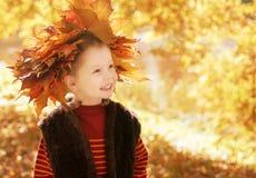 La petite fille avec la guirlande de l'érable laisse se reposer Photos stock