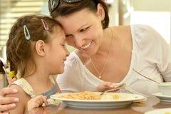 La petite fille avec la mère mange Images stock