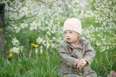 La petite fille avec la trisomie 21 dans la bouche tire des pissenlits Images stock