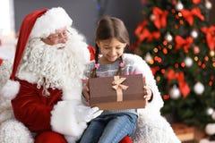 La petite fille avec le boîte-cadeau se reposant sur le ` authentique de Santa Claus enroulent à l'intérieur image libre de droits