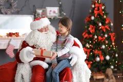 La petite fille avec le boîte-cadeau se reposant sur le ` authentique de Santa Claus enroulent à l'intérieur photos libres de droits