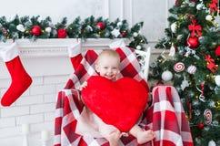 La petite fille avec le grand coeur rouge s'assied dans une chaise près de l'arbre de Noël Images stock