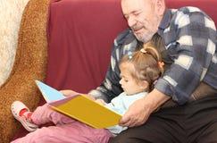 La petite fille avec le grand-père a lu le livre Image libre de droits