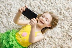 La petite fille avec le téléphone portable se trouve sur le tapis Photo stock
