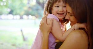 La petite fille avec les besoins spéciaux ont plaisir à passer le temps avec la mère Images stock