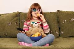 La petite fille avec les verres 3d mangent des puces Images libres de droits
