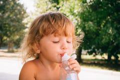 La petite fille avec plaisir d'or bouclé de cheveux boit l'eau pour Photo libre de droits